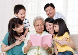 Large family of 5 huddling around an elderly woman reading from a pink book.